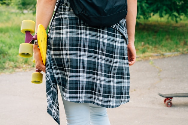 Chica recorre el parque con un monopatín en las manos.