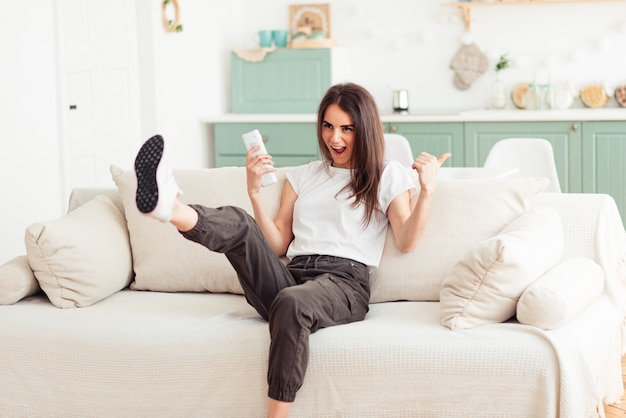 Chica recostada en un sofá y viendo tv