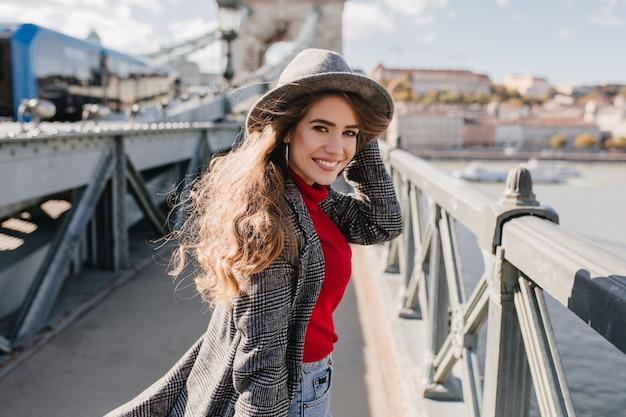 Chica refinada en elegante abrigo de tweed posando con una sonrisa encantadora sobre fondo urbano durante el viaje
