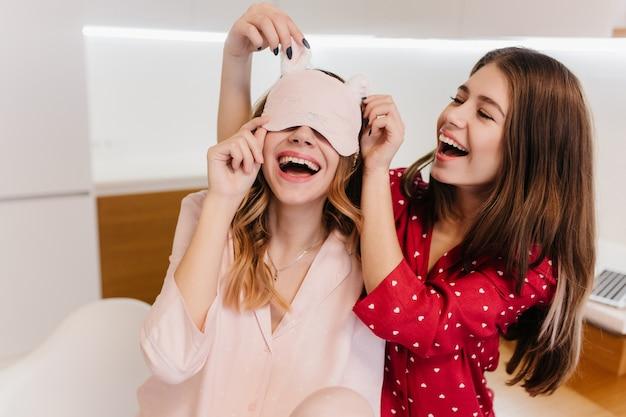 Chica refinada en traje rosa lleva antifaz en la mañana riendo en la cocina. foto interior de una mujer bonita morena en pijama rojo jugando con su hermana.