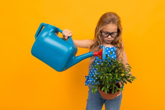 Chica regando una planta de interior en maceta en un amarillo con espacio de copia