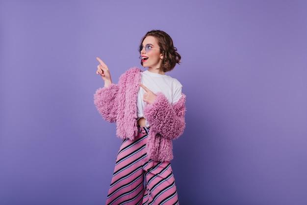 Chica relajada en pantalones de rayas rosas divirtiéndose. modelo de mujer de ensueño lleva abrigo de piel y gafas de sol bailando en la pared púrpura.
