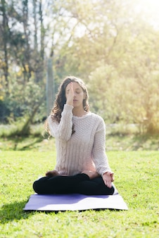 Chica relajada practicando yoga al aire libre