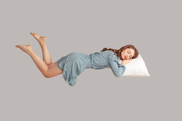 Chica relajada en vestido levitando en el aire, durmiendo boca abajo acostada cómoda y acogedora en la almohada