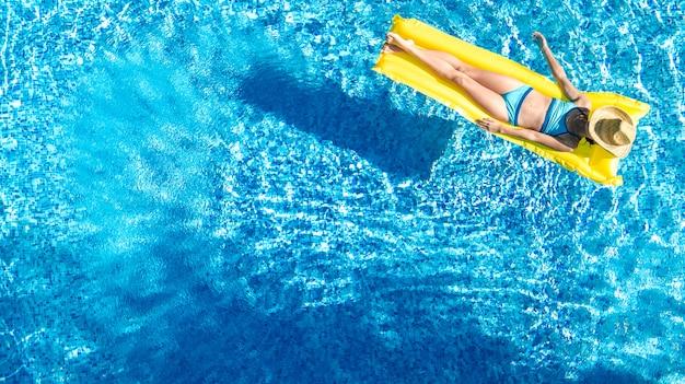 Chica relajándose en la piscina, el niño nada en un colchón inflable y se divierte en el agua en vacaciones familiares, resort tropical, vista aérea desde aviones no tripulados