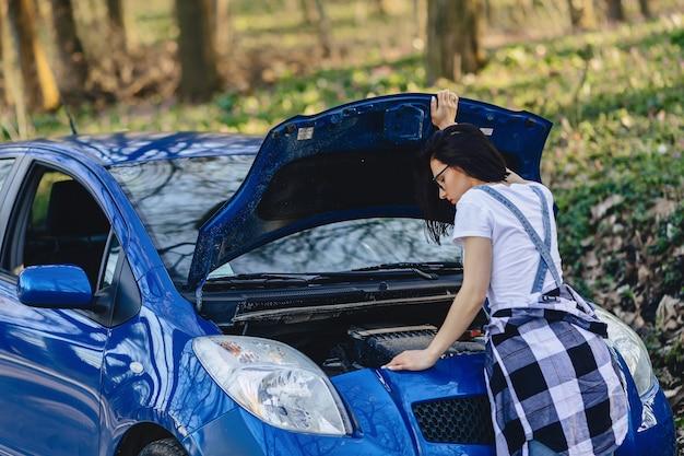 Chica repara carro con capó abierto en carretera.