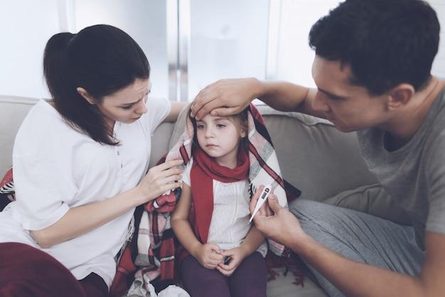 Chica se resfrió. su madre y su padre la están tratando.