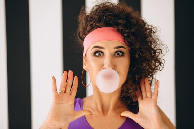Chica retro soplando burbujas con chicle