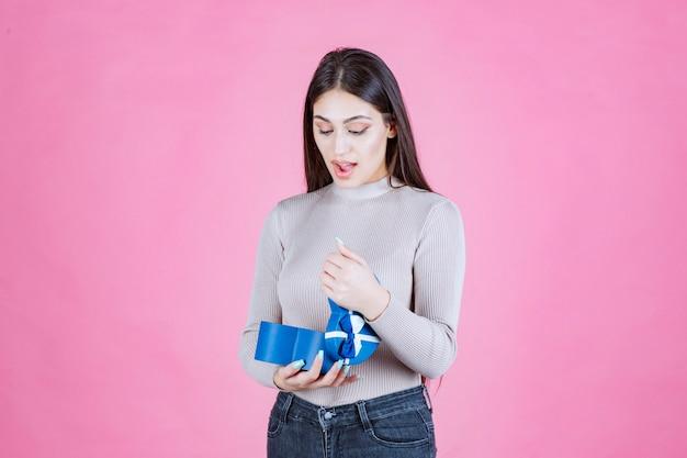Chica revisando su caja de regalo azul y mirando emocionada y sorprendida