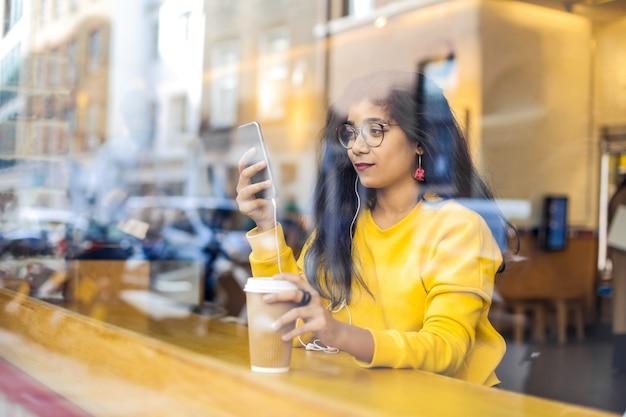 Chica revisando su teléfono, sentada en un café