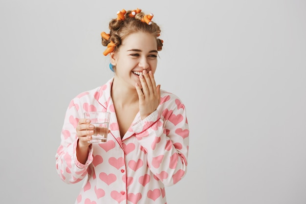 Chica riendo alegre en rizadores de pelo y pijama bebiendo un vaso de agua
