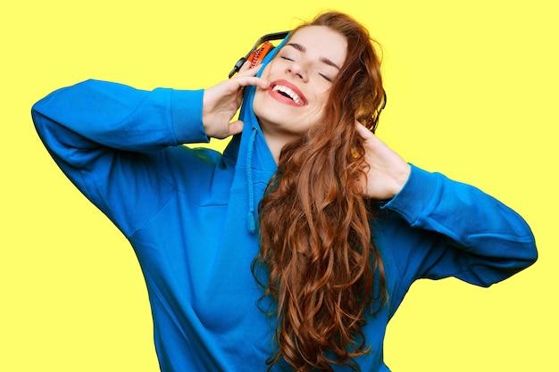 Chica riendo dj en chaqueta azul escuchando música en auriculares rojos sobre fondo amarillo