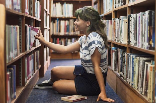 Chica riendo tomando un libro de la biblioteca