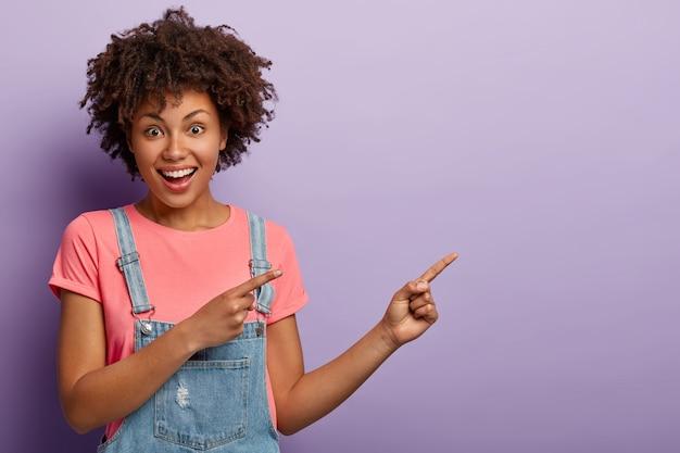 La chica rizada afroamericana alegre y emocionada da paso a un lugar increíble, señala a un lado, sonríe ampliamente, mira felizmente a la cámara, hace gestos contra el fondo púrpura