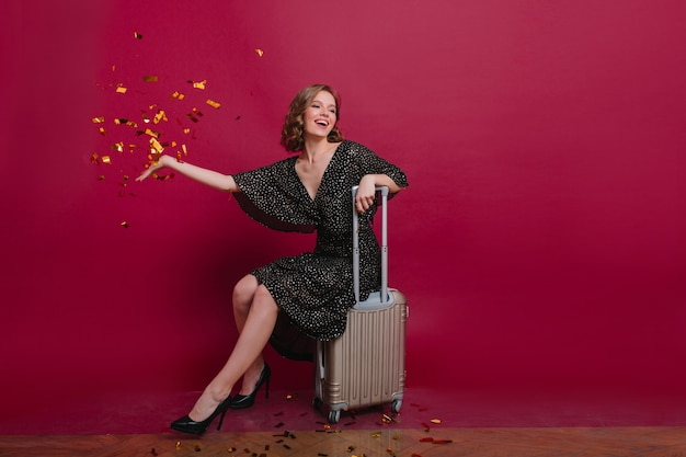 Chica rizada alegre en vestido negro retro descansando después de empacar la maleta para el próximo viaje