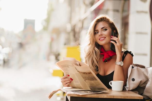 Chica rizada entusiasta mirando hacia arriba con una sonrisa mientras habla por teléfono en la cafetería al aire libre