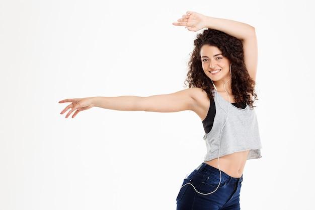 Chica rizada fitness escuchando música y posando