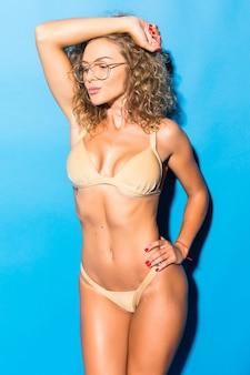 Chica rizada joven fitness en traje de baño está de pie sexy y coqueteando como modelo en la pared de la pared azul