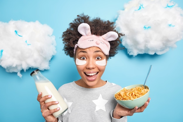 La chica rizada positiva usa antifaz y pijama para tomar un desayuno saludable posa alrededor de las nubes contra la pared azul disfruta de los buenos días
