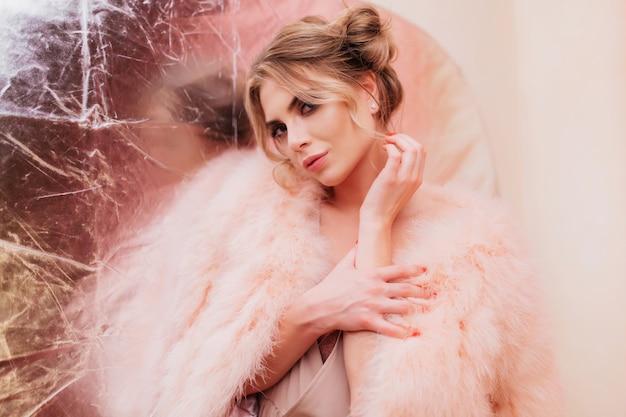 Chica rizada sensual en abrigo de piel rosa de moda se ve coquetamente y toca su mano. retrato de mujer joven rubia adorable en traje mullido con mucho gusto posando sobre fondo plateado brillo