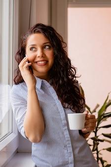 Chica rizada sosteniendo una taza de té y hablando por teléfono