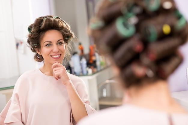 Chica con rizadores para el cabello mirando en el espejo