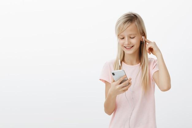 Chica robó el teléfono de mamá para ver la nueva serie de dibujos animados favoritos. niña juguetona complacida con cabello rubio, escuchando música en auriculares y sonriendo en la pantalla del teléfono inteligente mientras juega