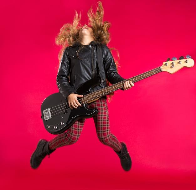 Chica de rock and roll rubia con bajo de guitarra salta en rojo