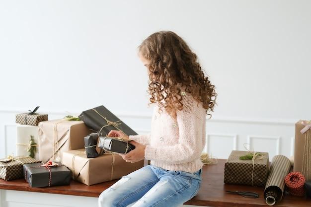 Chica rodeada de cajas de regalo.