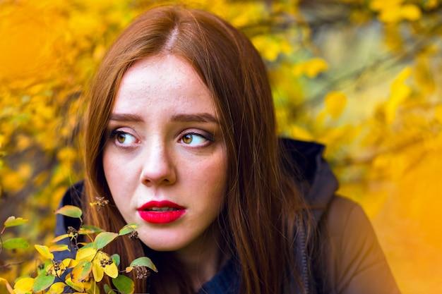 Chica romántica con cabello lacio brillante mirando a otro lado, escondiéndose detrás de un follaje amarillo. retrato al aire libre del primer del modelo femenino morena solitario que presenta en el parque del otoño.