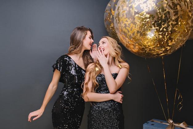 Chica romántica con cabello largo rubio sonriendo y cubriendo la boca con la mano. encantadoras damas con vestidos brillantes que se divierten juntas durante el evento.