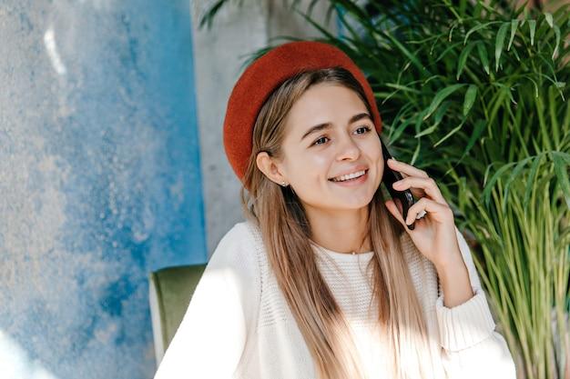 Chica romántica de ojos oscuros hablando por teléfono. atractiva mujer caucásica en boina llamando amigo.