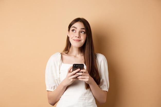 Chica romántica pensando con teléfono, mirando a un lado y sonriendo soñadora, usando la aplicación de citas en el teléfono inteligente, de pie en beige.