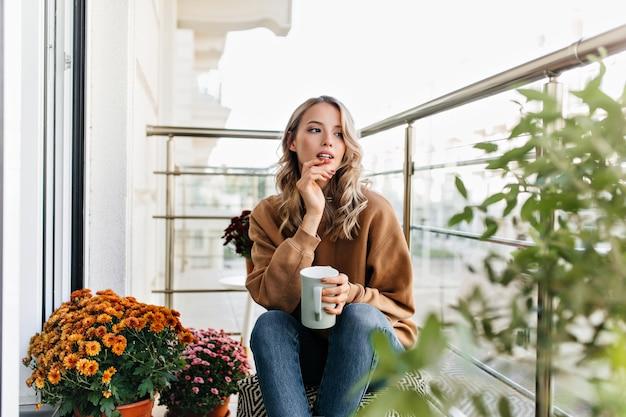 Chica romántica sentada cerca de flores con taza de café. mujer joven despreocupada pensando en algo.