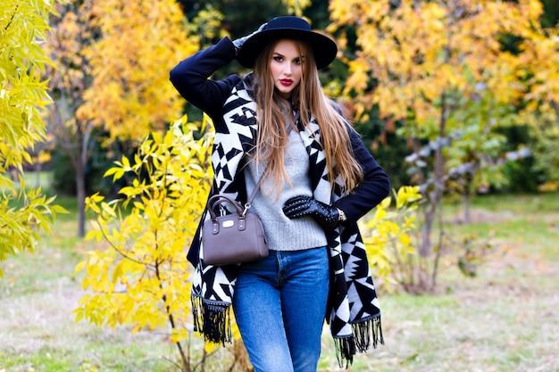 Chica romántica en vasos con sombrero y posando con expresión de cara de besos de pie en medio del parque. retrato al aire libre de linda mujer joven con bufanda de moda divirtiéndose durante la caminata en el bosque.