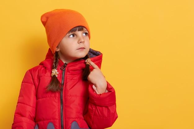 Chica con ropa de abrigo contra la pared amarilla apuntando a sí misma con el dedo, pensando, centrado en una tarea, mirando a un lado
