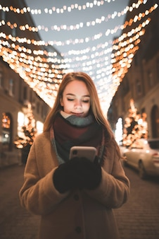 Chica en ropa de abrigo de pie al aire libre sobre un fondo de luces bokeh y usa un teléfono inteligente
