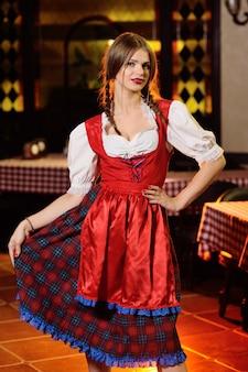Chica en ropa bávara en oktoberfest sobre fondo pub