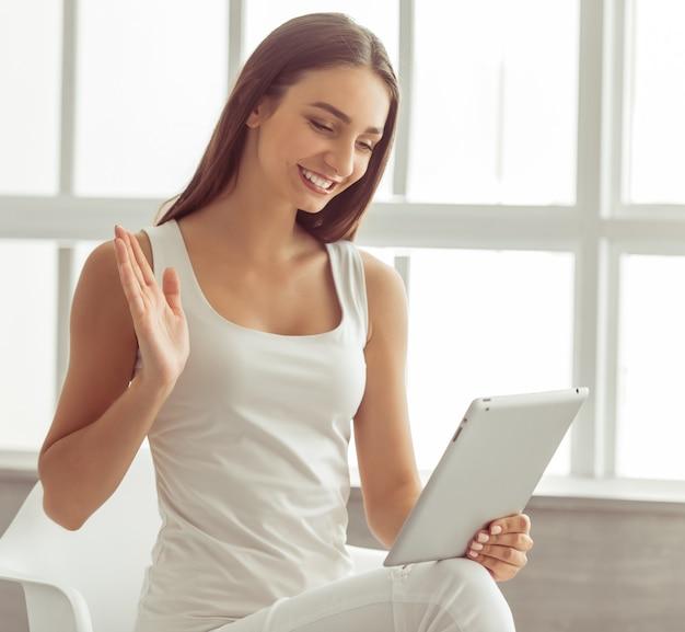 Chica en ropa casual blanca está utilizando una tableta digital.