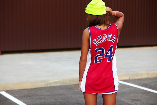 Chica en ropa deportiva de baloncesto rojo sentado sobre asfalto