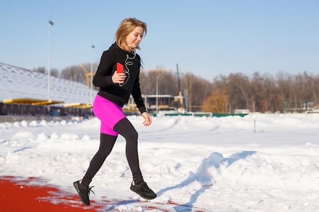 Chica en ropa deportiva corre en la pista roja para correr en un estadio cubierto de nieve ajuste y estilo de vida deportivo. correr y escuchar música. estilo de vida deportivo