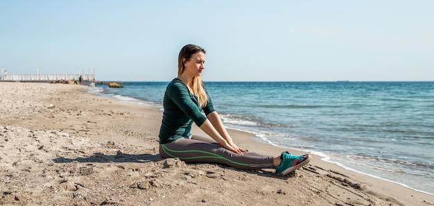 Chica en ropa deportiva fitness junto al mar escuchando
