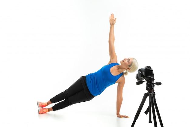 Chica en ropa deportiva haciendo deporte delante de la cámara en blanco