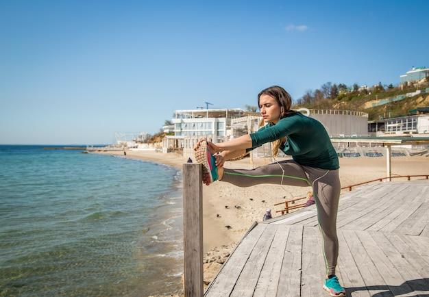 Chica en ropa deportiva haciendo estiramientos junto al mar