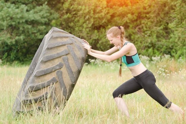 Chica en ropa deportiva levanta neumático grande