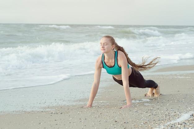 Chica en ropa deportiva de pie en un bar en la playa, las olas en el fondo.