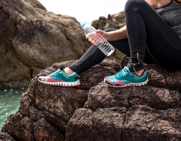 Chica en ropa deportiva en las rocas