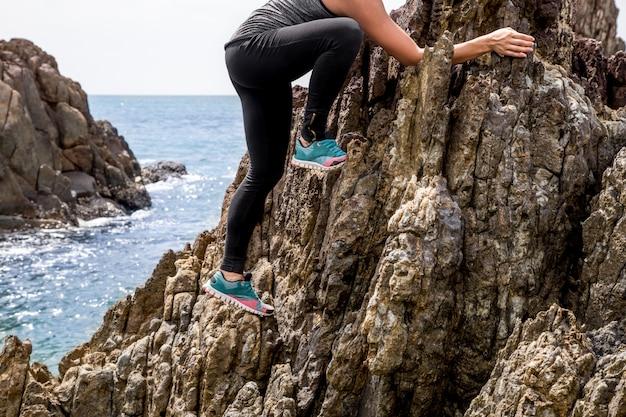 La chica en ropa deportiva en las rocas