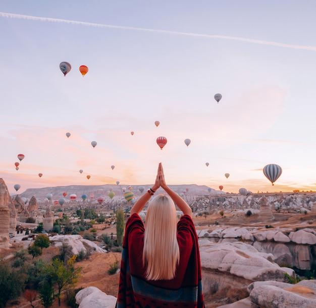 Chica en ropa étnica al amanecer viendo el vuelo, muchos globos vuelan sobre el valle del amor