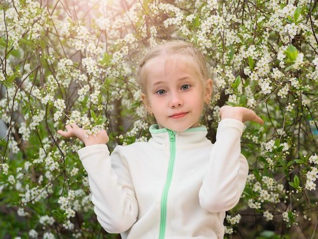 Chica en ropa de gimnasia en un árbol de cerezo en flor